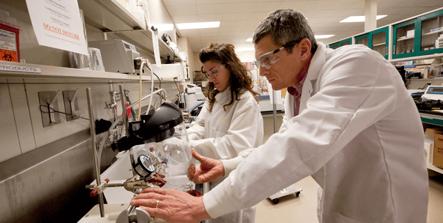 Jim, a senior engineer, pressure tests catheters with Demetra, a Co-Op student, in the Engineering Testing Laboratory.