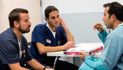 Amro and Chris, members of the Cook Surgery team, talk to a surgeon.
