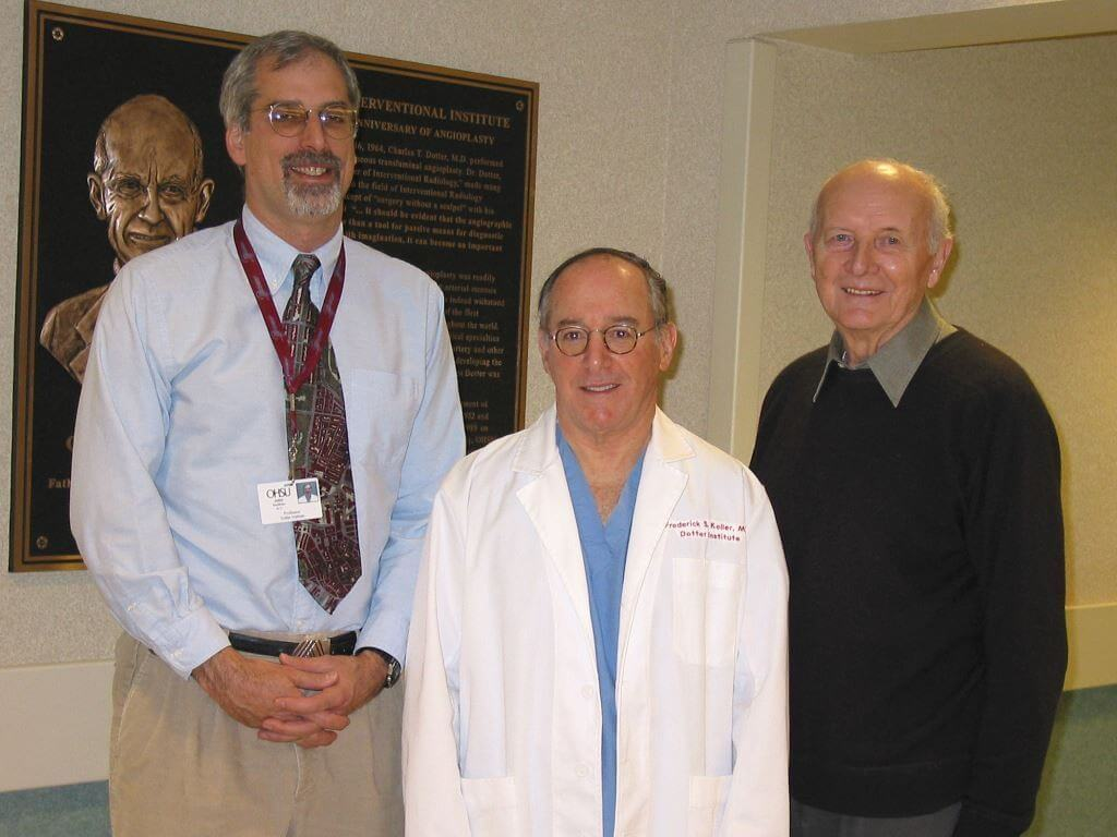 Three Dotter Interventional Institute directors: Dr. John Kaufman, the current director; Dr. Frederick Keller, past director; and Dr. Josef Rösch, founding director; in front of a plaque depicting Dr. Charles T. Dotter.